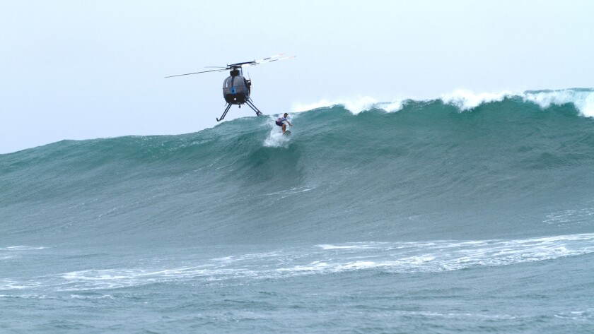 """Nathan Fletcher surfs off Hawaii on April 21, 2017, with a helicopter hovering above, in the documentary """"Heavy Water."""""""