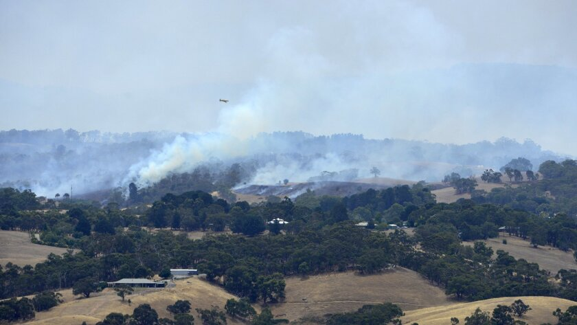 A plane flies over smoke from fires burring across the Adelaide Hills, near Adelaide, Australia, Saturday, Jan. 3, 2015.  Thousands of Australians fled their homes as wildfires raged across the nation's south on Saturday, with firefighters struggling to contain the blazes as strong winds fanned the