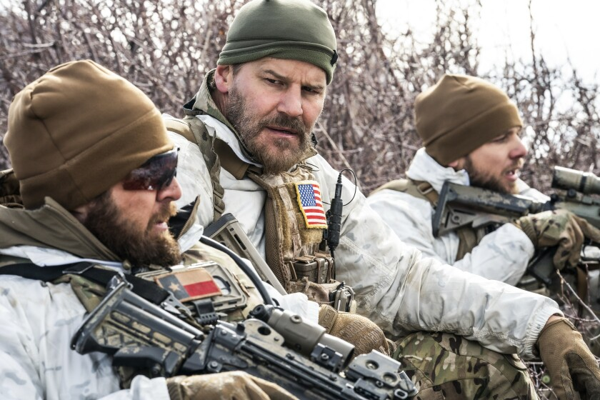 """Three men in the woods wearing camouflage and holding rifles in """"SEAL Team"""" on CBS."""