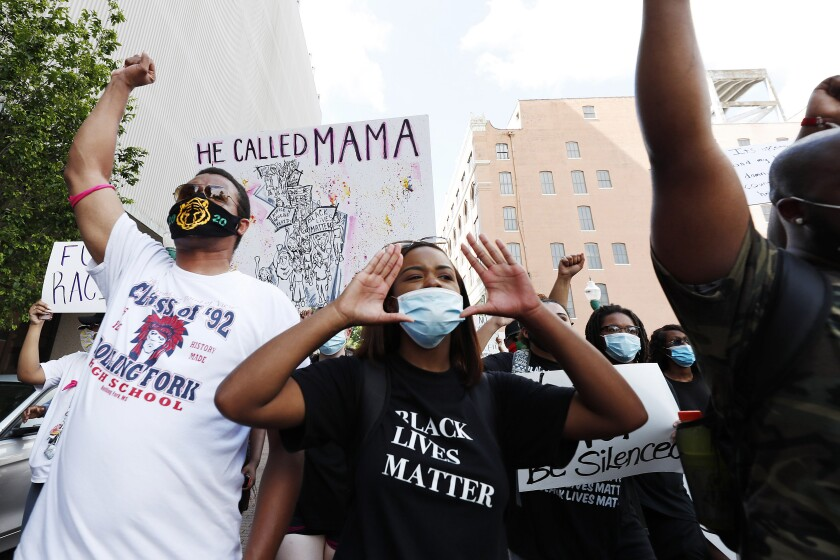 In this June 6, 2020, photo, Maisie Brown, 18, second from left, a member of the Mississippi branch of Black Lives Matter, leads a protest march with others during a rally in Jackson, Miss., over police brutality. Young activists like Brown are energizing the debate about removing the Confederate battle emblem from the Mississippi state flag. Brown says elected officials must step up and change the flag. (AP Photo/Rogelio V. Solis)
