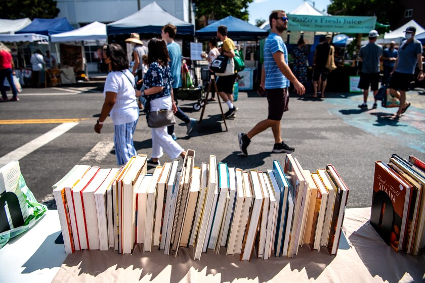 People walk past an array of cookbooks for sale on a table at an outdoor market.