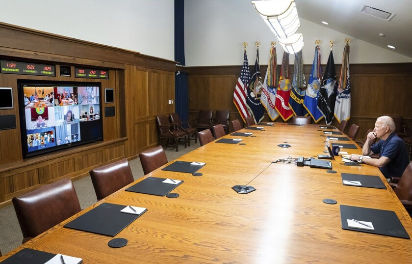 President Biden sits at a long table and watches a screen for a virtual meeting.