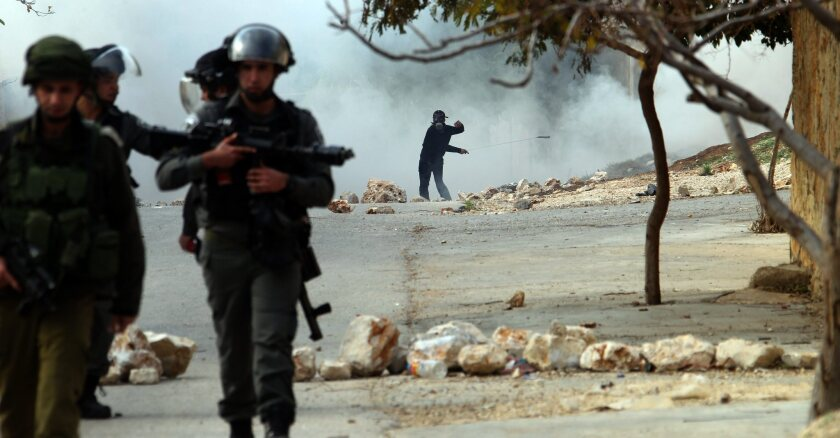 A Palestinian protester hurls stones at Israeli soldiers Friday during clashes over the Jewish settlement of Qadomem, near the West Bank city of Nablus. Israel announced plans Friday to build at least 1,400 new homes in Jewish settlements in the West Bank and pursue further developments in Jerusalem, which could put more strain on peace talks with the Palestinians.