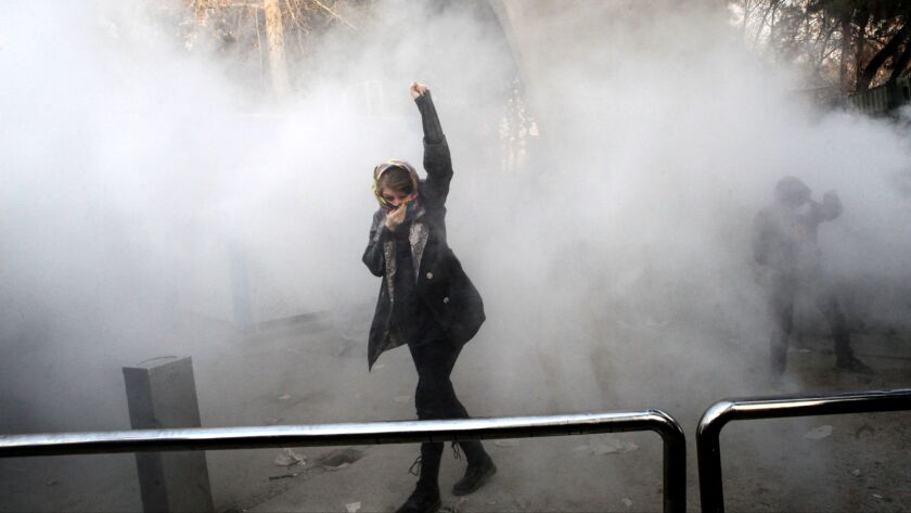 An Iranian woman raises her fist amid the smoke of tear gas at the University of Tehran during a protest on Dec. 30.