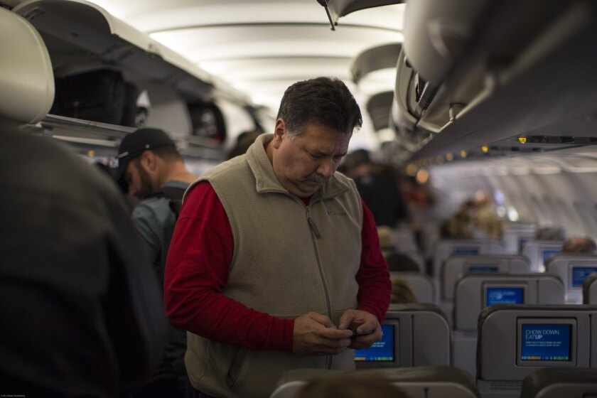 A passenger on a JetBlue Airways plane checks his cellphone before leaving Long Beach. Members of Congress have signed a letter urging federal regulators to keep a ban on cellphone calls on planes in place.