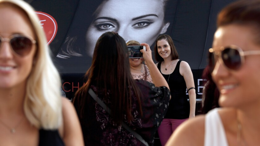 Fans of Adele have their picture taken next to a photo of the singer at the first of her eight night sold out shows at Staples Center.