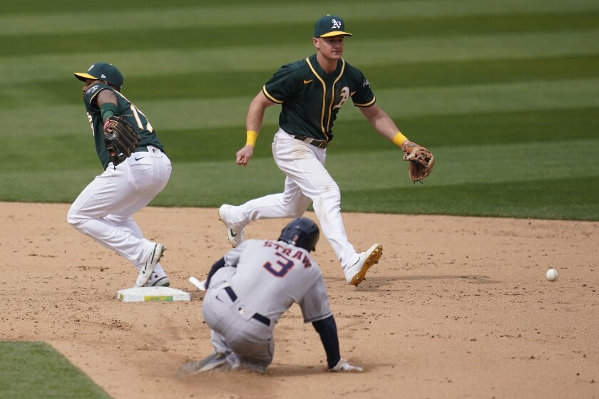 Oakland Athletics shortstop Elvis Andrus, left, cannot field a throwing error by third baseman Matt Chapman, top, as Houston Astros' Myles Straw (3) advances to second base during the sixth inning of a baseball game in Oakland, Calif., Sunday, April 4, 2021. (AP Photo/Jeff Chiu)