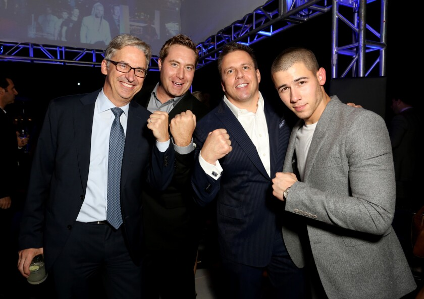 "Daniel York, left, shown with AT&T executives Bart Peters and Chris Long, celebrate the season premiere of DirecTV's ""Kingdom"" with actor Nick Jonas."