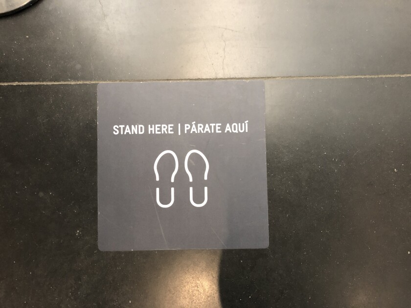 """A floor marker shows the outline of two feet and the words """"Stand Here / Párate Aquí"""""""