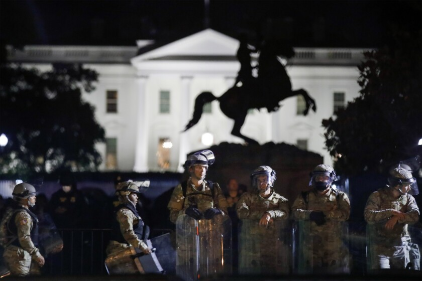 A line of DC National Guard members stand in Lafayette Park as demonstrators gather to protest the death of George Floyd, Tuesday, June 2, 2020, near the White House in Washington. Floyd died after being restrained by Minneapolis police officers. (AP Photo/Alex Brandon)