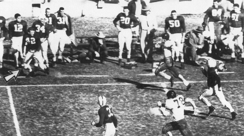 File-This Jan. 1, 1954, file photo shows Alabama fullback Tommy Lewis (42) (arrow) coming off the bench getting ready to tackle Rice halfback Dicky Moegle (47), as he crosses the 50 yard line during the Cotton Bowl at Arlington, Tex., Jan. 1, 1954. Maegle, the Rice running back tackled in the 1954 Cotton Bowl by an Alabama player who came off the bench in one of the most legendary plays in college football history, has died. Rice and the National Football Foundation both said Tuesday, July 6, 2021, that Maegle passed away Sunday. He was 86. (Tom Dillard/The Dallas Morning News via AP)