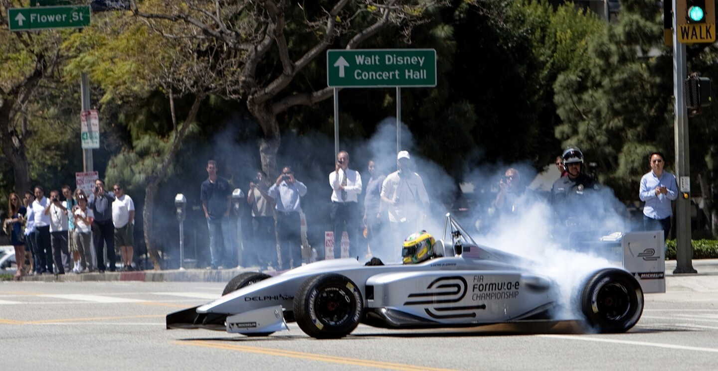 Driver Lucas di Grassi spins his wheels making turns while demonstrating the new Formula E electric race car prototype on Hope Street in downtown L.A.
