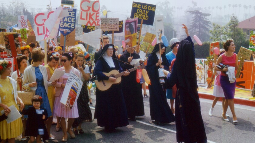 Nuns lead a procession featuring colorful handmade signs.