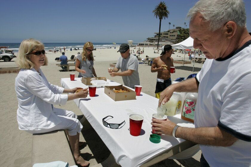 Larry Newberry pours lemonade with family at Moonlight State Beach. He and his wife Sharon recently arrived from Missouri for a vacation with their daughter Lindy Burrow and her husband Carl Burrow and their son Jordan Burrow, who live in Carmel Valley.