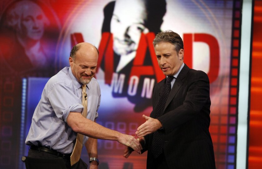 "FILE - In this March 12, 2009 file photo, Jim Cramer, left, host of the CNBC ""Mad Money"" show, is welcomed by host Jon Stewart during an appearance on Comedy Central's ""The Daily Show with Jon Stewart"" in New York. After hosting nearly 2600 editions, Stewart will sign off for good on Aug. 6. (AP Photo/Jason DeCrow, FIle)"