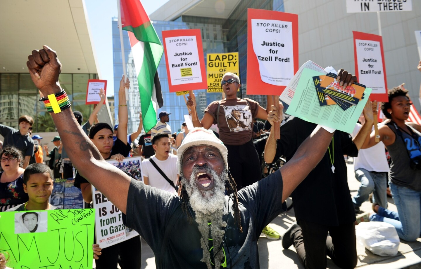 Kelly Kunta leads a rally outside Los Angeles Police Department headquarters in downtown L.A. on Sunday to protest police killings of young black men around the country.