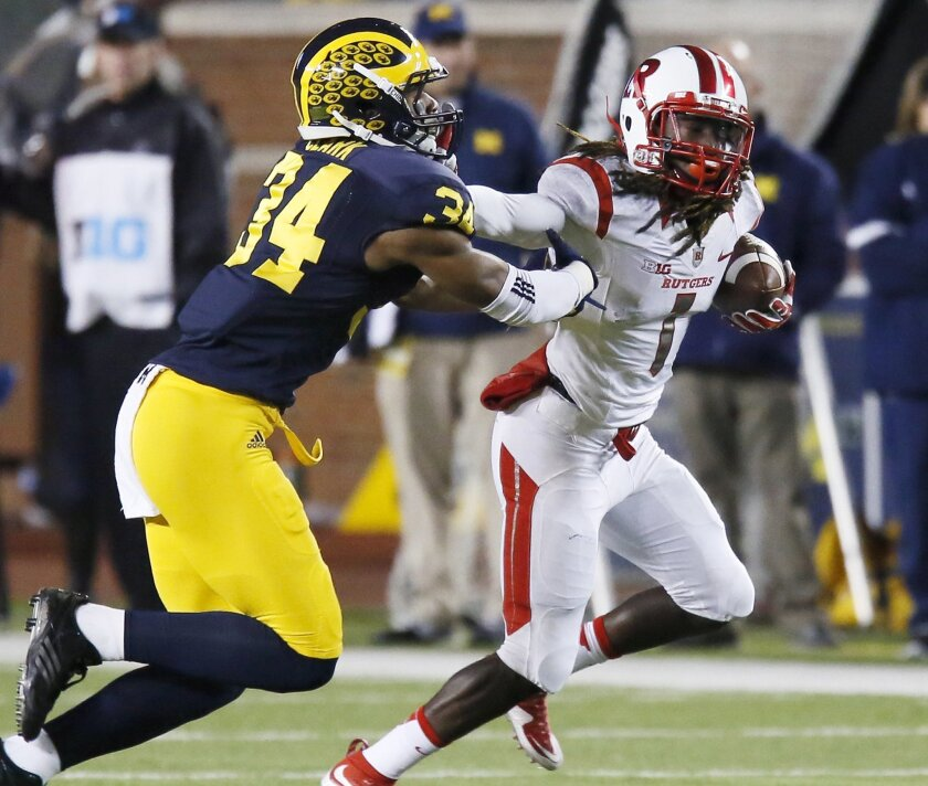 Rutgers' Janarion Grant (1) is pursued by Michigan's Jeremy Clark (34) during the second half of an NCAA college football game Saturday, Nov. 7, 2015, in Ann Arbor, Mich. Michigan defeated Rutgers 49-16. (AP Photo/Duane Burleson)