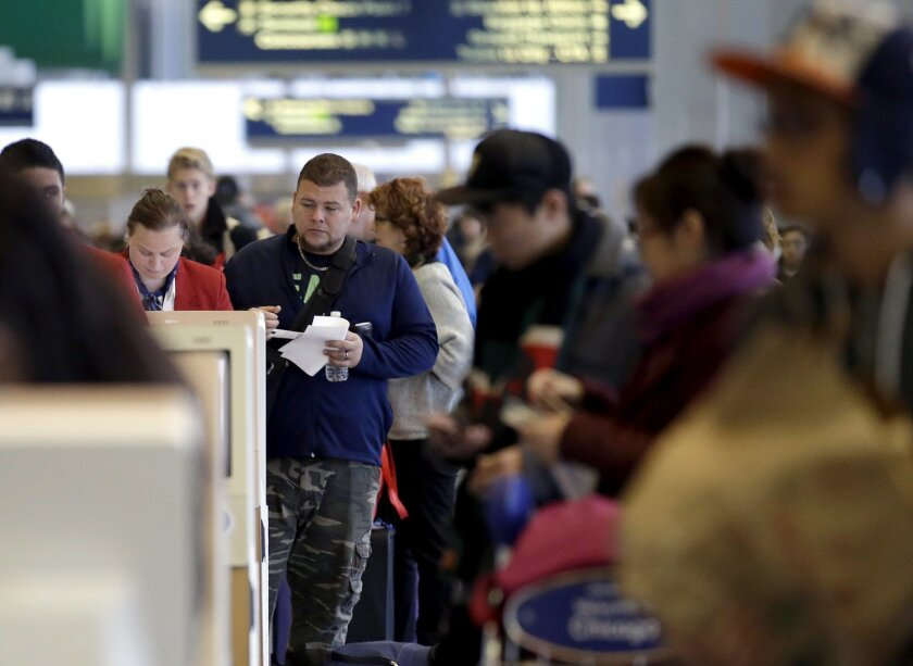 Travelers check their tickets and walk to their gates at O'Hare International Airport on Sunday, Nov. 29, 2015, in Chicago. Tens of millions of Americans returning home after the long Thanksgiving holiday weekend Sunday have cooperative weather and mostly efficient airport operations to thank for s