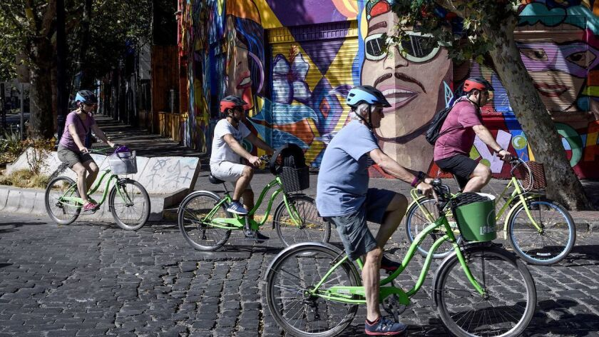 SANTIAGO, CHILE – FEBRUARY 3, 2019: A group of tourist ride their rent bicycles in Bellavista neighb