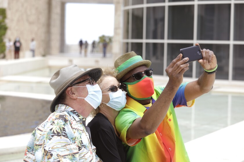 Three people wearing masks take a selfie outside the Getty Center