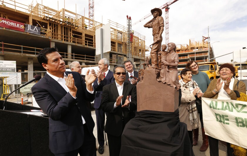 Los Angeles City Councilman Jose Huizar, left, applauds the unveiling of a scale model of a 19-foot monument depicting a Mexican bracero and his family.