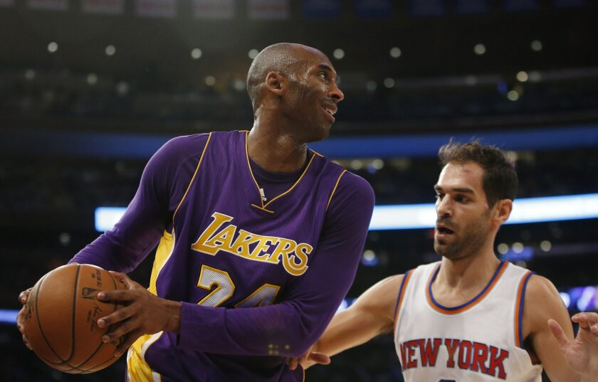 Los Angeles Lakers forward Kobe Bryant (24) keeps the ball from New York Knicks guard Jose Calderon (3) as he looks to pass in the first half of an NBA basketball game at Madison Square Garden in New York, Sunday, Nov. 8, 2015.  (AP Photo/Kathy Willens)