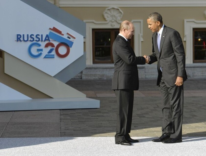 Presidents Obama and Putin exchange greetings during a procession of world leaders at the gold- and cream-colored Konstantinovsky Palace in St. Petersburg.