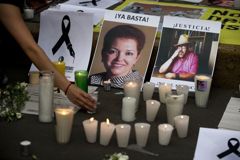 una mujer coloca una vela frente a las fotografías de los periodistas asesinados Miroslava Breach