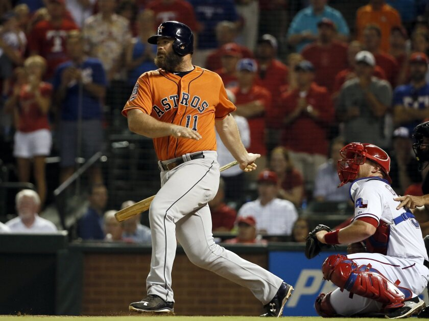 FILE - In this Sept. 15, 2015, file photo, Houston Astros' Evan Gattis follows through on a two-run single as Texas Rangers catcher Chris Gimenez watches during the fourth inning of a baseball game in Arlington, Texas. Injured Houston designated hitter Evan Gattis and the Astros have avoided salary