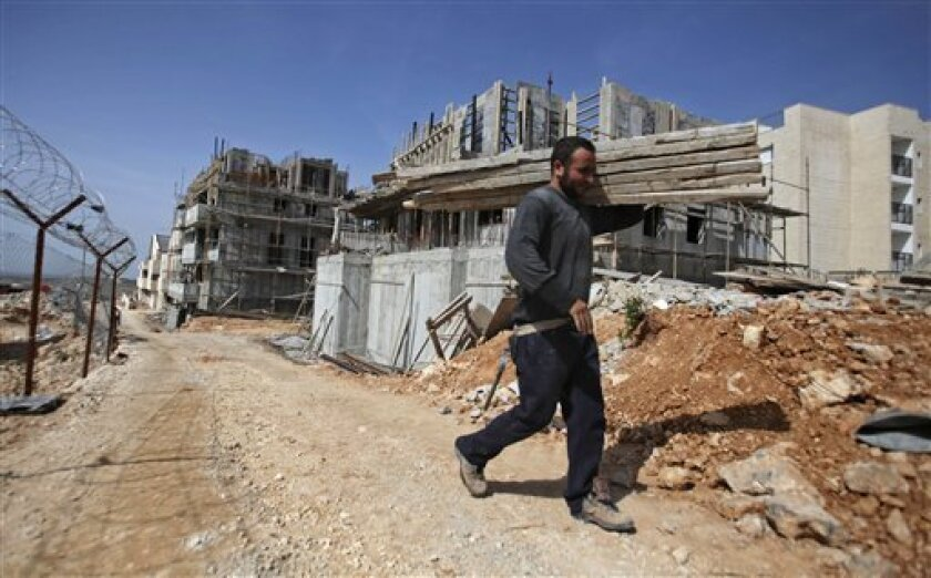 A Palestinian man works at a housing construction site in the Jewish settlement of Beitar Illit, near Jerusalem, Monday, March, 8, 2010. Israel has authorized the construction of 112 new apartments in the West Bank despite a settlement slowdown, the government disclosed Monday _ a decision that enr