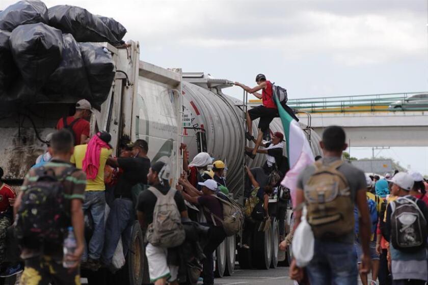 Migrantes hondureños suben a vehículos que se encuentran en el camino para continuar otro tramo del territorio mexicano rumbo a su objetivo principal, Estados Unidos, tras haber pasado la noche en la ciudad de Tapachula, en Chiapas (México) hoy, lunes 22 de octubre de 2018. EFE