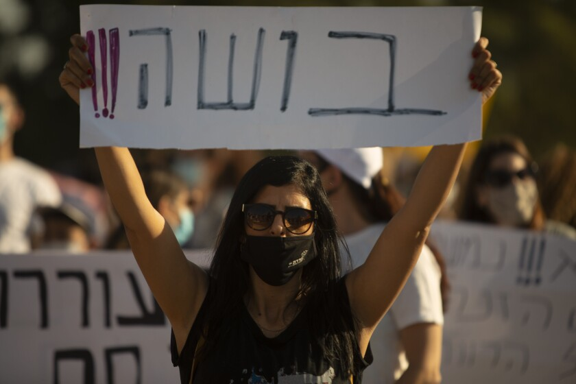 """An Israeli social worker holds a sign in Hebrew that reads, """"shame,"""" during a protest against the economic situation in the central Israeli town of Kfar Ahim, Thursday, July 9, 2020. With a new outbreak of coronavirus devastating Israel's economy, one of Prime Minister Benjamin Netanyahu's closest confidants was dispatched on to a TV studio on a recent day to calm the nerves of a jittery nation. Instead, he dismissed the public's economic pain as """"BS.""""(AP Photo/Sebastian Scheiner)"""