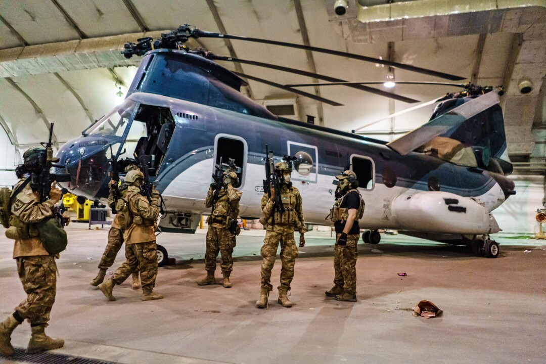 Fighters inside a hangar next to a military helicopter