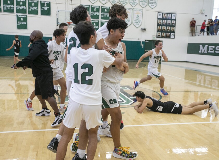 The Costa Mesa High School boys' basketball team celebrates after beating Valley Village Valley Torah on Friday.