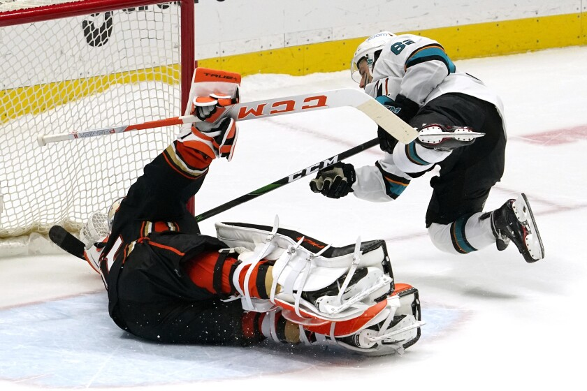 San Jose Sharks right wing Kevin Labanc, right, scores on Anaheim Ducks goaltender John Gibson during the shootout in an NHL hockey game Friday, Feb. 5, 2021, in Anaheim, Calif. The Sharks won 5-4. (AP Photo/Mark J. Terrill)