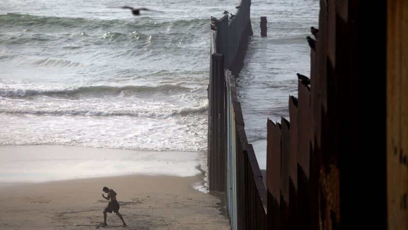 The existing U.S.-Mexico border wall extends into the ocean at Playas de Tijuana, separating California from Baja California.