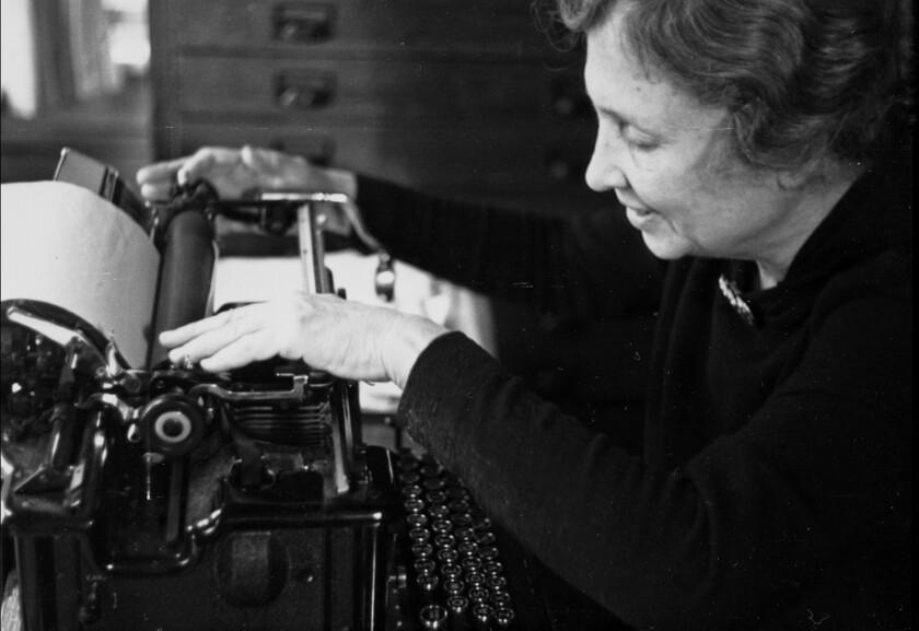 Helen Keller sits at a typewriter.