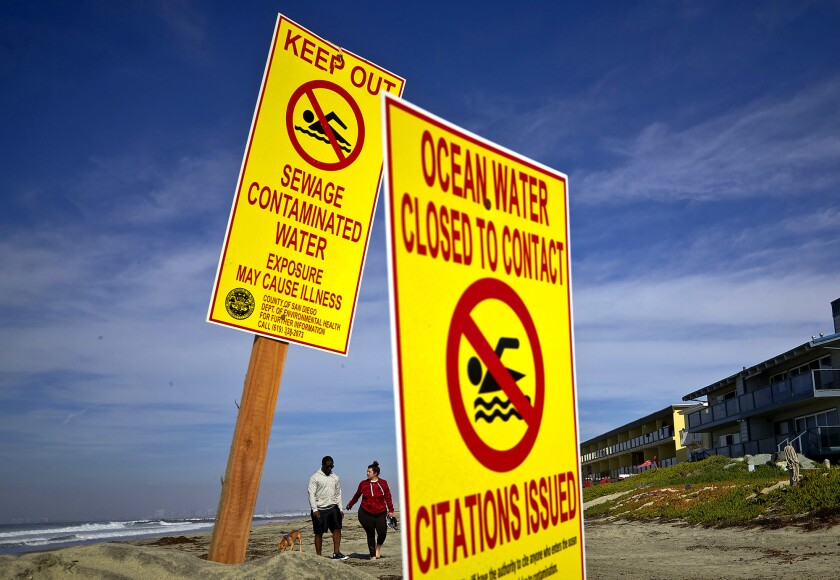 A couple walks along Imperial Beach, Calif., on Wednesday as signs warn of contaminated water.