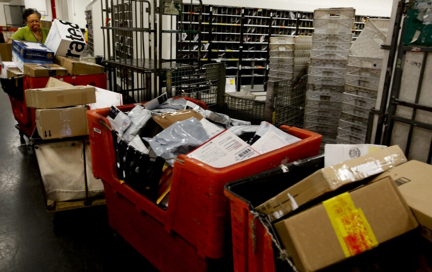 A supervisor moves packages behind the scenes at the U.S. Postal Service's Airport Station.