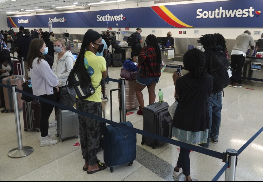Passengers queue up at the ticketing counter for Southwest Airlines flights Sunday, Oct. 10, 2021, in Omaha, Neb.