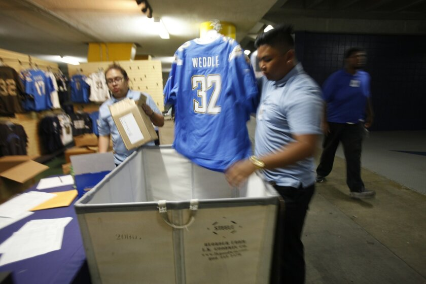 Delaware North salesperson Benjamin Reyes, right, puts away jersey that won't be availbe until the next home game at Qualcomm Stadium.