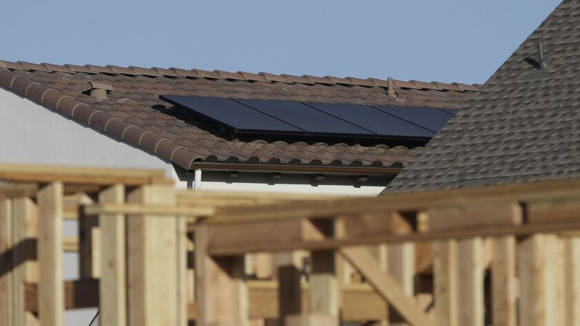 In this photo taken Monday, May 7, 2018, solar panels are seen on the rooftop on a home in a new hou