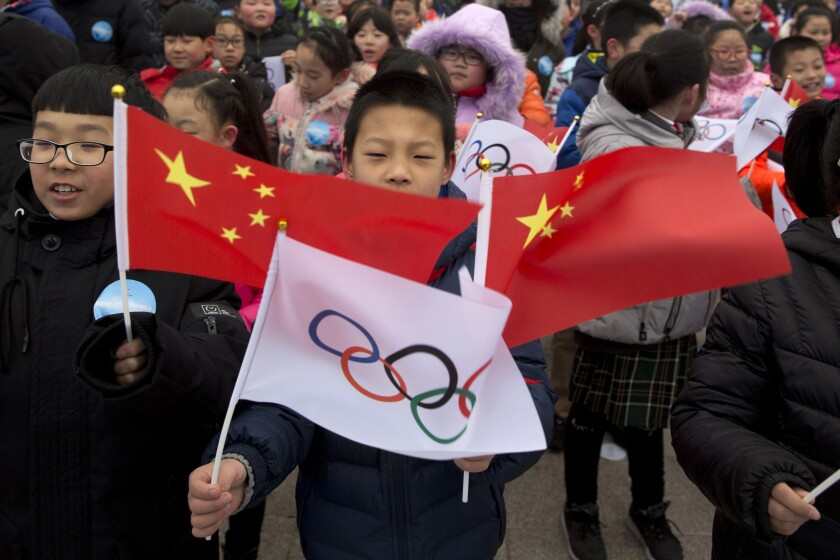 A child waves a Chinese national flag and an Olympic flag during a ceremony in February 2018 for the 2022 Winter Olympic Games in Beijing.