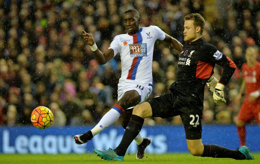 Crystal Palace's Yannick Bolasie, left, battles for the ball with Liverpool goalkeeper Simon Mignolet during the English Premier League soccer match at Anfield, Liverpool, England, Sunday Nov. 8, 2015. (Martin Rickett/PA via AP) UNITED KINGDOM OUT