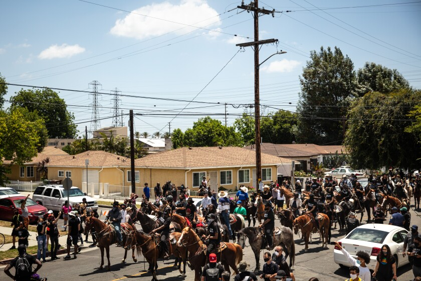 The Compton Cowboys ride down South Tamarind Avenue, along with protesters, during the Compton Peace Ride.