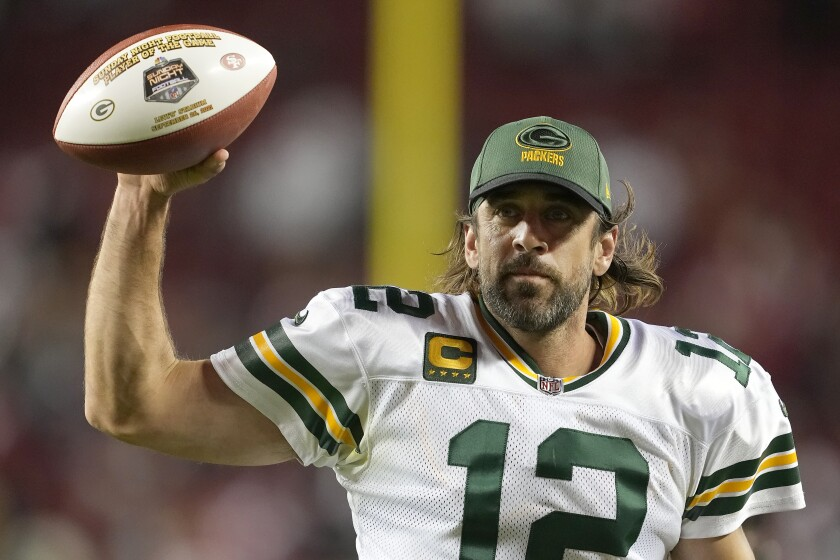 Green Bay Packers quarterback Aaron Rodgers holds up game ball after leading late rally for win Sunday night.