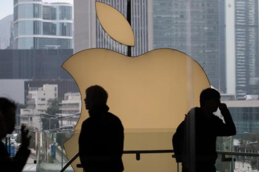 Clientes caminan junto al logotipo de Apple. EFE/ Jerome Favre/Archivo