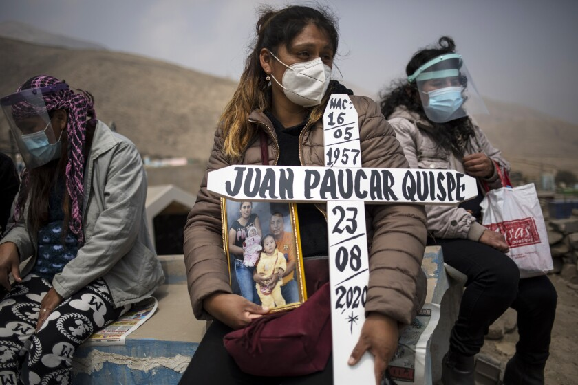 Ruth Morales waits for the coffin of her husband, Juan Paucar Quispe, who died from COVID-19, at a cemetery in Lima, Peru.