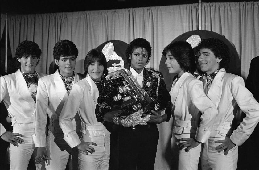 En esta foto del 28 de febrero de 1984, Michael Jackson, en el centro, posa entre bambalinas con el grupo Menudo