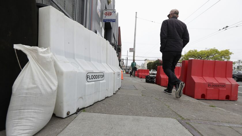 A man walks between flood barriers on 17th Street in San Francisco, Thursday, April 5, 2018. Norther